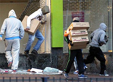 Looters carry boxes out of a home cinema shop in central Birmingham during the riots