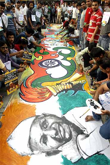 Supporters of Anna Hazare paint a sketch during a protest against corruption