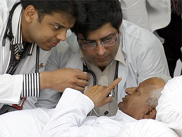 Anna Hazare speaks to doctors as they examine him at Ramlila Ground in New Delhi