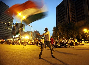A supporter of Anna Hazare waves India's national flag during a protest march