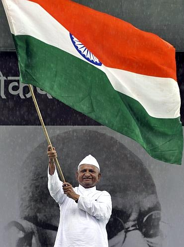 Social activist waves the tricolour during his indefinite fast to press for a stronger Lokpal Bill at Ramlila Ground in Delhi
