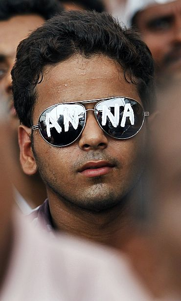 A supporter of veteran activist Anna Hazare wears sunglasses bearing his name