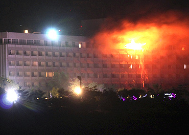 Smoke and flames rise from the Intercontinental hotel during a battle between NATO-led forces and suicide bombers and Taliban insurgents in Kabul on June 29