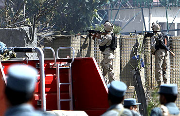 Afghan commando troops and policemen take up position at the site the suicide attack in Kabul