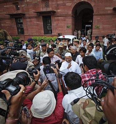 Anna Hazare and Arvind Kejriwal wave to the media after a joint Lokpal drafting committee meeting in New Delhi