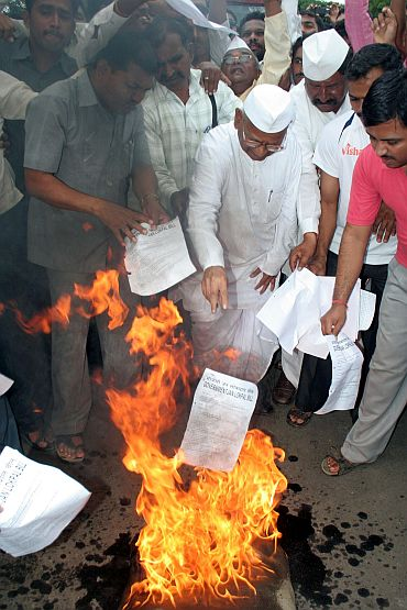 Social activist Anna Hazare burns copies of the government's Lokpal Bill