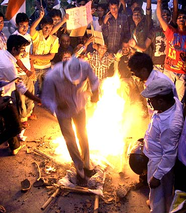Supporters of Indian social activist Anna Hazare burn an effigy depicting corruption during a protest against corruption in the northern Indian city of Allahabad