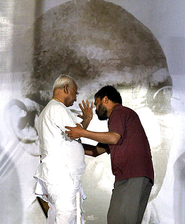 Anna Hazare (L) is helped by one of his supporters on the eighth day of his fast at Ramlila grounds in New Delhi
