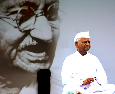 Anna Hazare greets a supporter as he sits in front of a portrait of Mahatma Gandhi, at Ramlila grounds in New Delhi