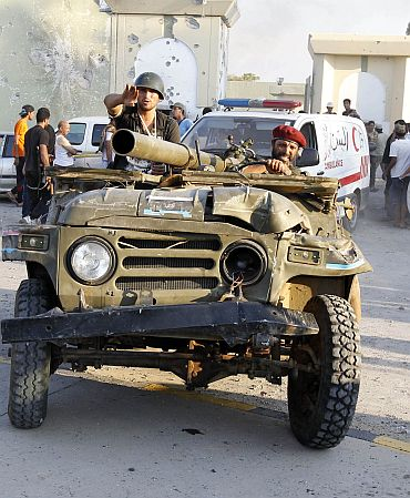 Libyan rebels ride a vehicle at Bab Al-Aziziya compound in Tripoli