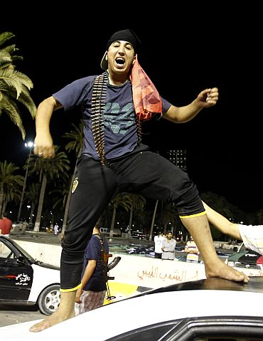 A Libyan rebel fighter celebrates in Green Square, renamed Martyrs Square by rebels, in Tripoli