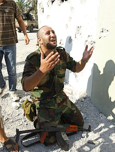 A Libyan rebel fighter prays at the enterance of Bab al-Aziziya compound in Tripoli