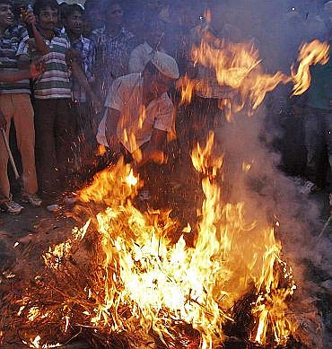 Supporters of Anna Hazare burn an effigy representing corruption during a protest rally in Ahmedabad
