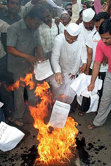 Anna Hazare and his supporters burn copies of the government version of Lokpal Bill