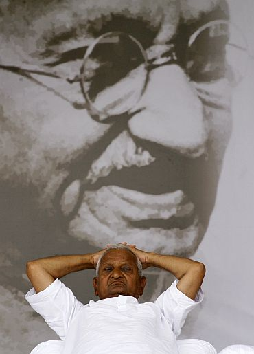 Anna Hazare rests in front of a portrait of Mahatma Gandhi