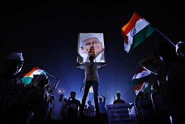 A Hazare supporter holds his portrait on the ninth day of Hazare's fast at Ramlila grounds in New Delhi