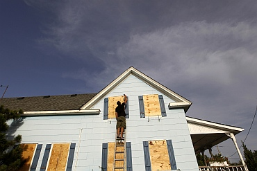 A man boards up the windows of his friend's house at Cape Hatteras National Seashore in Salvo, North Carolina