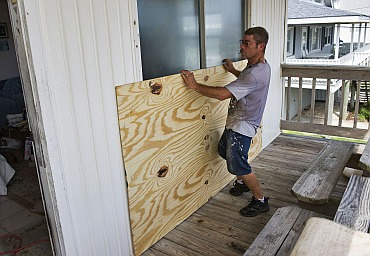 A man positions a sheet of plywood over a sliding glass door as he boards up a house in preparation for Hurricane Irene in Atlantic Beach