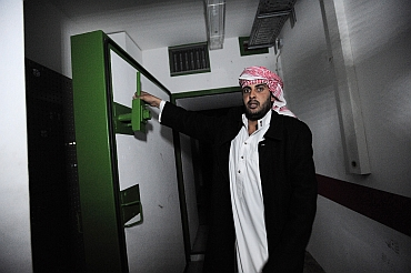 A Libyan man shows a door in the extensive underground tunnels running under Gaddafi's residence