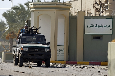 A rebel fighter is seen at the south gate of the Bab al Aziziya compound as they make a final push to flush out pro-Gaddafi forces from the compound in Tripoli. The sign on the wall reads Welcome, our dear guest