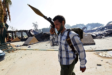 A rebel fighter is seen at the south gate of the Bab al Aziziya compound