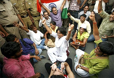 Supporters of Anna Hazare shout slogans outside the residence of Prime Minister Manmohan Singh
