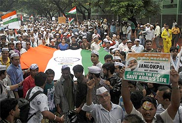 Supporters of activist Anna Hazare carry the national flag during a rally against corruption