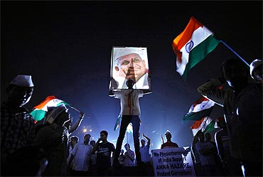 A supporter of Anna Hazare holds his portrait
