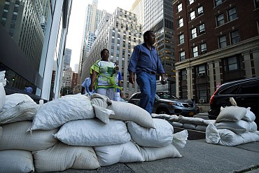 Pedestrians pass sandbags used to control possible floods at downtown Manhattan in New York