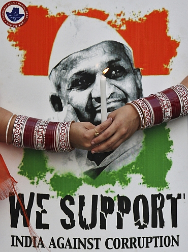 A supporter of Hazare holds a candle and his portrait during a candlelight protest against corruption in Chandigarh