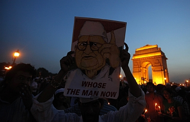 A supporter holds a portrait of Hazare in front of India Gate during the celebrations after the Gandhian ended his fast in New Delhi