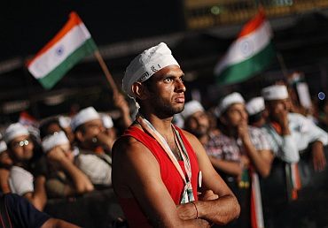 A supporter of Indian social activist Hazare listens to a speech during Hazare's fast in New Delhi