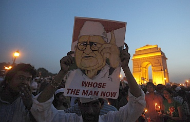 A supporter holds a portrait of Hazare in front of India Gate during the celebrations
