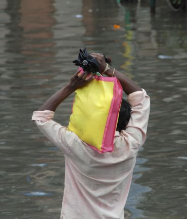 A man makes his way through a flooded street