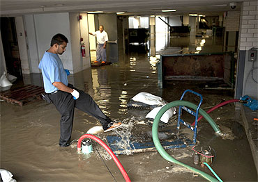 Hotel employees clear water from a flooded area of the Allegria Hotel after flooding from Hurricane Irene in Long Beach, New York