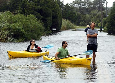 Residents use kayaks to navigate a flooded street in Southampton, New York