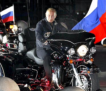 Russian Prime Minister Vladimir Putin rides with enthusiasts during his visit to a bike festival in the southern Russian city of Novorossiisk