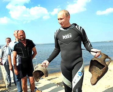 Putin carries artifacts he recovered whilst diving at an archaeological site off the Taman peninsular in southern Russia