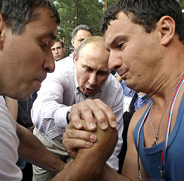 Putin adjudicates an arm-wrestling match during his visit to the summer camp of the pro-Kremlin youth group