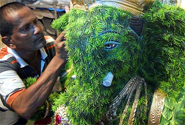 An artisan prepares a Ganesh idol out of blades of grass