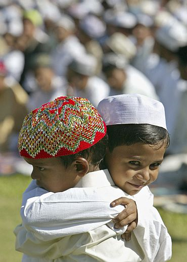 Muslim children hug each other after offering prayers