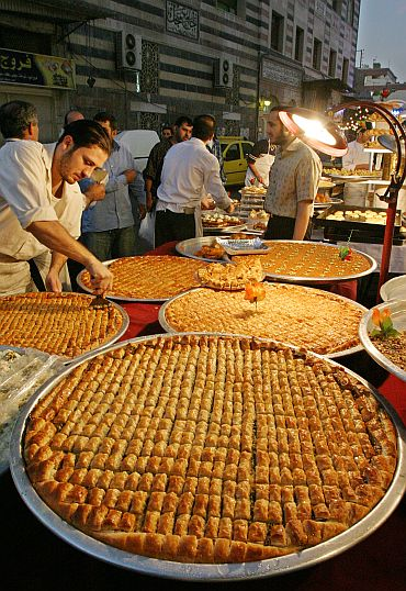 A Syrian seller displays Arabic sweets to sell at an old Damascus market