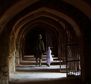 A man and a boy hold hands as they walk through a corridor under the ruins of the Feroz Shah Kotla Mosque in New Delhi after prayers