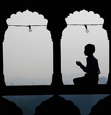 A Muslim boy prays as others gather during morning prayers at the Jama Masjid