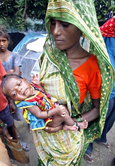 File picture of a woman holding her newborn baby at a flood relief camp in Bihar.