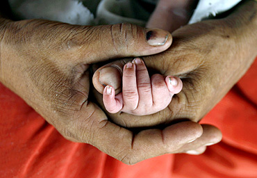 A woman holds the hand of her newborn child in Akhera village in Haryana