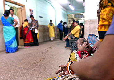 A woman holds a newborn waiting for a routine check-up at a hospital in Kolkata