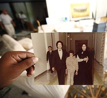 A Libyan shows a photograph of Muammar Gaddafi, his son Seif al Islam and his wife Safia at Hannibal's house in Tripoli August 30