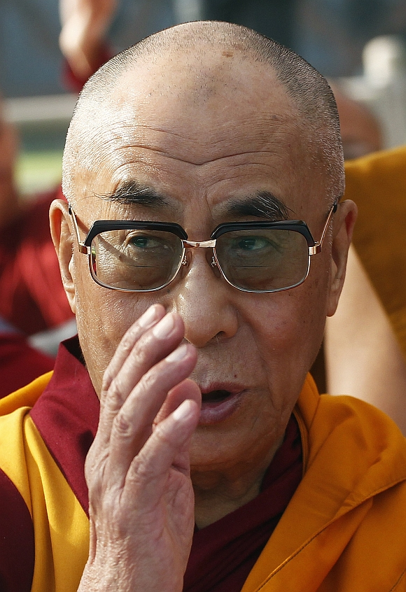 Tibetan spiritual leader the Dalai Lama prays during an all faith prayer meet