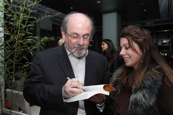 Salman Rushdie signs a copy of his latest book Luka and the Fire of Life